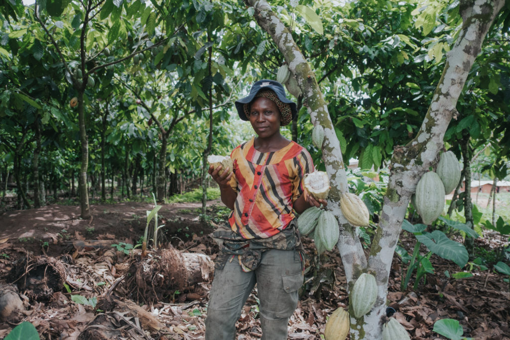 photo of woman ni a colorful shirt standing in a wooded area holding cocoa pods